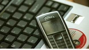 Stock photograph of a mobile phone and computer keyboard