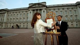 The Queen's Press Secretary Ailsa Anderson and footman Badar Azim posting the royal baby birth notification in front of Buckingham Palace.