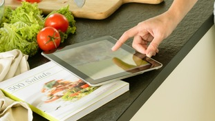Woman using tablet recipe book searching kitchen wine vegetables.