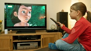 A girl watches a film on television.