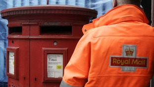 Royal Mail postman collecting from a post box