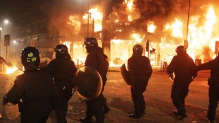 Police officers watching a shop burn during 2011 riots