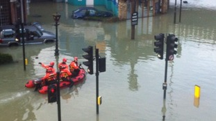 Rescue teams use a dinghy through the flooded streets in Herne Hill