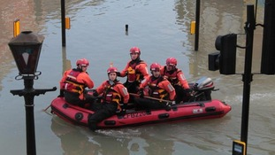 Team from the London Fire Brigade make their way through a flooded Herne Hill