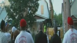 People watch as diggers move in to destroy Ariel Castro's home.