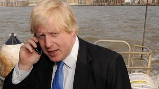 Boris Johnson guards his smartphone on a London Thames clipper