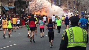 Runners continuing to run towards the finish line of the Boston Marathon as an explosion erupted near the finish line of the race.