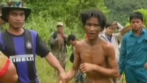 Ho Van Lang, 42, is led out of the jungle after four decades living in isolation