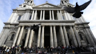 eople sit on the steps of St Paul's Cathedral as it reopens in London October 28, 2011.