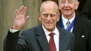 The Duke of Edinburgh waves to crowds.