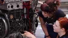 Apprentices study a cutaway model of a car engine