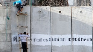 Two Palestinians climb over the security barrier