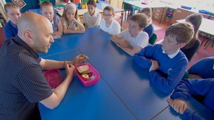Man shows lunch-box to assorted kids in classroom