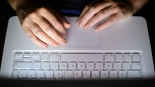 Stock photograph of a person typing on a computer keyboard.