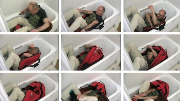 "Images issued by the Metropolitan Police of a video reconstruction showing an ""expert"" trying to lock himself in a sports bag unaided."