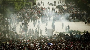 Muslim Brotherhood supporters run away from tear gas during clashes in Cairo on Friday