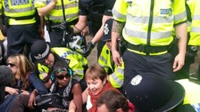Caroline Lucas MP is seen in the centre wearing a red scarf surrounded by police