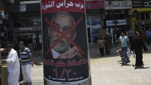 A poster of Muslim Brotherhood spiritual leader Mohamed Badie with the words, ch reads 'Together to down Brotherhood's power'.