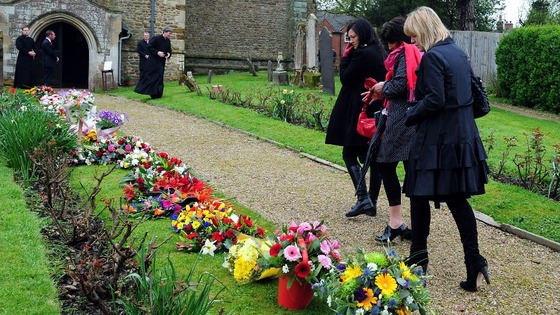 Mourners look at floral tributes as they attend the funeral of Claire Squires