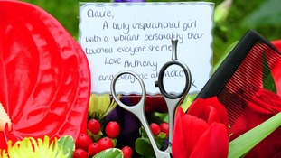 Scissors and a comb are left amongst floral tributes outside the funeral of hairdresser Claire Squires