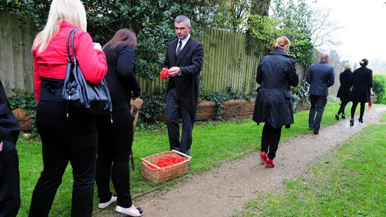 Mourners are handed red wristbands as they attend the funeral of Claire Squires at St Andrew's Church in North Kilworth