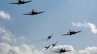 A group of eight Supermarine Spitfires fly above the Imperial War Museum airfield at Duxford.