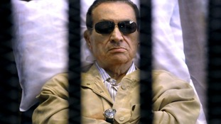 Egypt's deposed leader Hosni Mubarak appears in a cage at an earlier court hearing