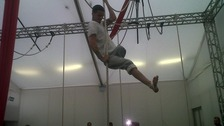 A performer hangs on a rope.