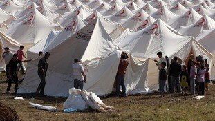 Syrian refugees set up a tent at a refugee camp in the Turkish border town of Boynuegin in Hatay province