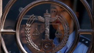 A policeman stands next to a glass pane at the court in Jinan where Bo Xilai is standing trial