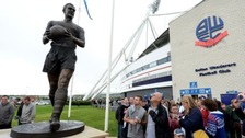 Fans look at the new Nat Lofthouse statue outside the Reebok Stadium