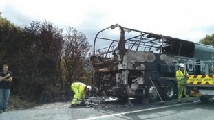 A metal shell is all that is left of the team coach after the fire this morning