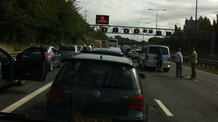 People get out of their cars as traffic hits a standstill on the M6