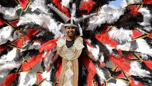 One entertainer wears an elaborate, richly-feathered costume