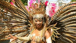 A carnival performer wears long feathers