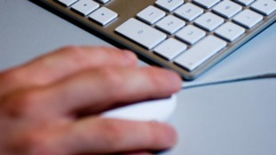 A person using a mouse and computer keyboard.