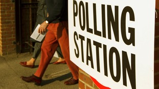 Two people walk out of a polling station.