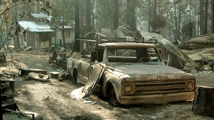 An out building and pickup truck damaged by the Rim Fire.