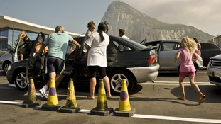 People stand outside their cars to cool down as they wait in queues on the Gibraltar side of the Spanish border
