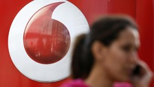 A woman talks on the phone with a Vodafone sign in the background.