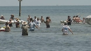 Diana Nyad can be seen swimming amid a crowd by Smathers Beach in Key West, Florida.