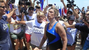 Diana Nyad looks shaky as she makes it to the beach unaided.