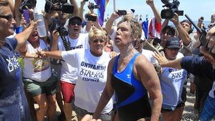 Diana Nyad looks shaky as she makes it to the beach unaided.