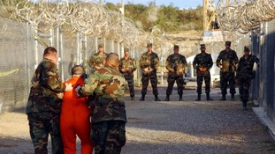 US Army military police escort a detainee in Guantanamo Bay in 2002.