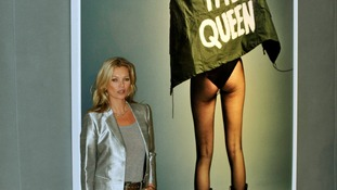 Kate Moss poses in front of an image by Craig McDean