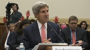 Secretary of State John Kerry seen with the protesters' hands in the background.