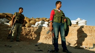 Free Syrian Army fighters stand with their weapons near the Kwers military airport.