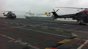 Two helicopters sit on the deck of HMS Ocean, while a ferry can be seen in the background.