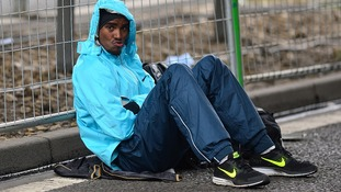 Mo Farah pouts for the cameras as he shelters from the rain.