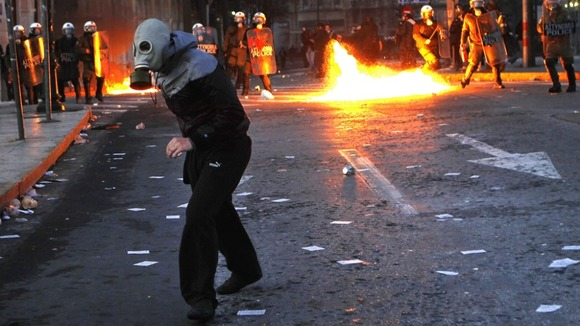 A protester runs away from police during a violent anti-austerity demonstration in central Athens